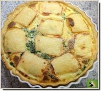 Tarte aux épinards recouverte de tranches de fromage à raclette